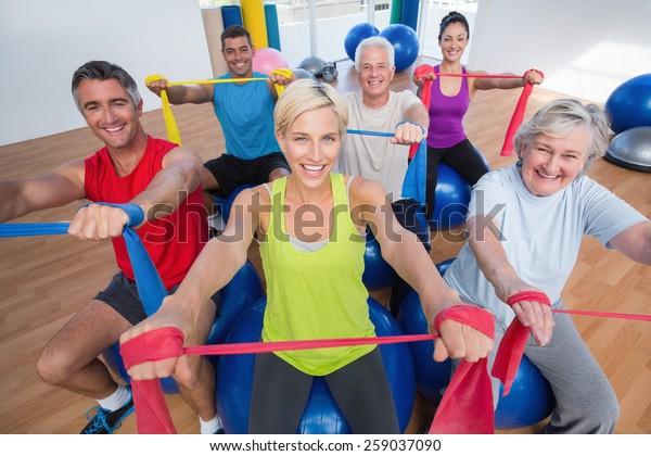 Portrét šťastných mužů a žen na fitness míčích cvičení s odbojovými kapelami v tělocvičně