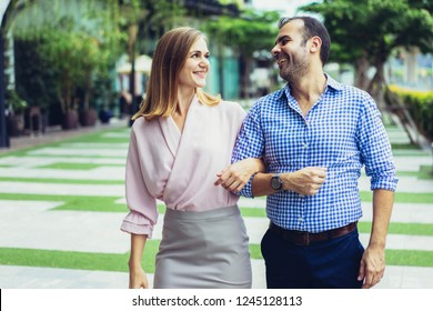Portrait of happy mid adult Caucasian couple walking arm in arm in street. Man and woman dressed in casual style dating outdoors. Relationship concept