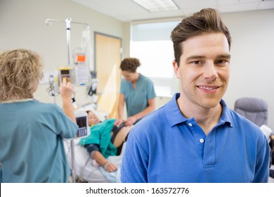 Portrait of happy mid adult man with nurses tending to birthing woman in background
