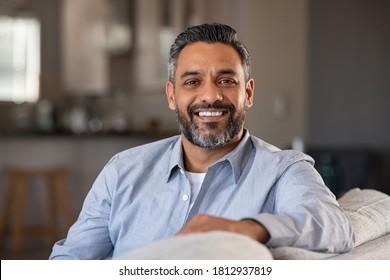 Porträt eines glücklichen, erwachsenen Mannes, der zu Hause auf dem Sofa sitzt. Schöner Latein Mann in lockerer Entspannung auf Sofa und Lächeln. Fröhlicher Indianer, der die Kamera anschaut.