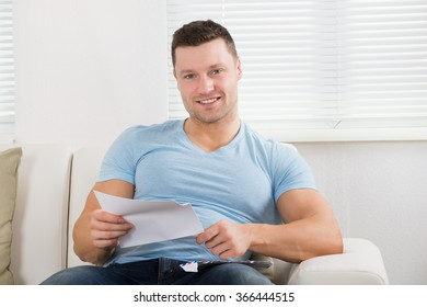 Portrait of happy mid adult man holding letter on couch at home