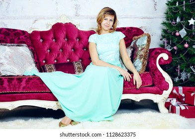 Portrait of happy mid adult woman sitting on luxurious sofa