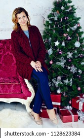 Portrait of happy mid adult woman sitting at Christmas tree
