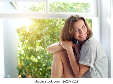 Portrait of a happy mid adult woman sitting by window at home. Relaxed woman smiling