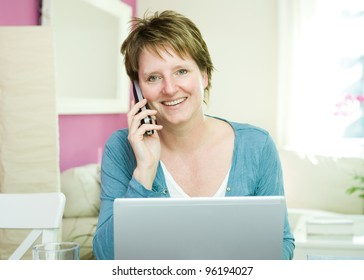 Portrait of happy middle age woman with phone and computer working at home