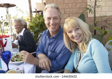 Portrait of happy middle aged couple having lunch outdoors