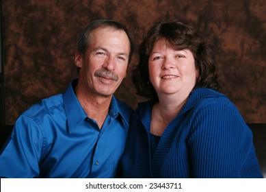 Portrait of a happy middle aged couple, wearing teal, against a brown mottled background.
