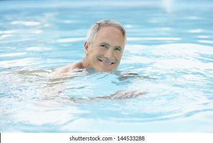 Portrait of happy middle aged man swimming in pool