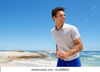 Portrait of a happy middle aged man walking on the beach