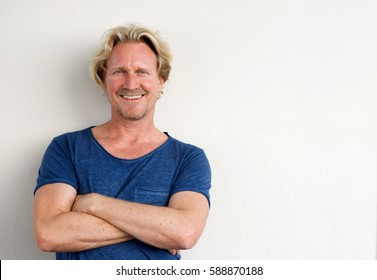 Portrait of happy middle aged man posing with arms crossed against white background