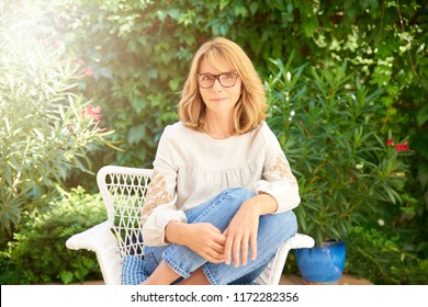 Portrait of happy middle aged woman wearing casual clothes and looking at camera while sitting in the garden and relaxing.