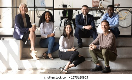 Portrait of happy middle aged and young coworkers sitting on stairs in modern office. Positive different generations mixed race business people enjoying informal communication in loft workplace.