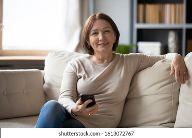 Portrait of happy middle-aged female sit rest on cozy sofa in living room look ta camera using modern cellphone, smiling senior woman smartphone user relax on couch at home posing, technology concept