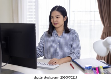 A portrait of a happy, middle-aged, long hair Asian woman working at home, using pc comuter, looking at screen, typing, and smiling. Remote working and technology concept.
