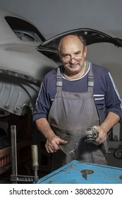Portrait of a happy middle-aged worker in his workshop.