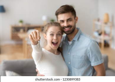 Portrait of happy millennial couple hug holding key to own apartment, young husband and wife excited to buy first home together, smiling married man and woman move in shared house. Ownership concept
