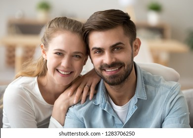 Portrait of happy millennial couple in love looking at camera, young man and woman dating posing at home, smiling boyfriend girlfriend or husband wife romantic relationships concept, head shot