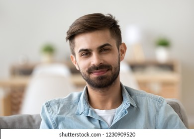 Portrait of happy millennial man looking at camera relaxing at home, headshot of smiling young male posing for picture indoors, confident guy making picture sitting on couch in apartment. Close up