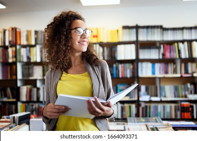 Portrait of happy mixed race college woman student at campus library