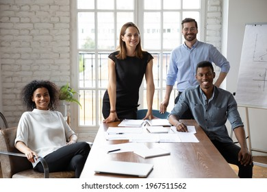 Portrait of happy mixed race motivated successful colleagues employees looking at camera, posing together in modern office, company staffing, international career opportunities, collaboration concept.