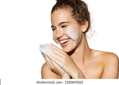 Portrait of happy model using foam for moisturizing skin. Beauty skincare and wellness concept. Copy space in left side. Studio picture on white background