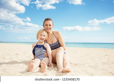 Portrait of happy modern mother and daughter in beachwear on the seacoast