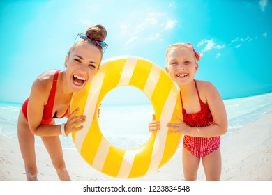 Portrait of happy modern mother and daughter in red swimwear on the seacoast holding yellow inflatable lifebuoy