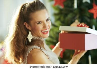 Portrait of happy modern woman near Christmas tree opening Christmas present box