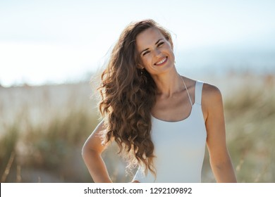 Portrait of happy modern woman in white swimsuit on the seashore. wild beach with green grass and no people. blue sky. minimal to no crowd peace. Sun protected hair. european woman.