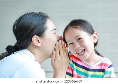Portrait of happy mom whispering a something secret to her little daughter ear on sofa at home. Mother and kid communication concept.