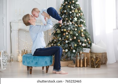 Portrait of happy mother and adorable baby celebrate Christmas. New Year's holidays. Toddler with mom in the festively decorated room with Christmas tree and decorations. Mother playing with baby boy