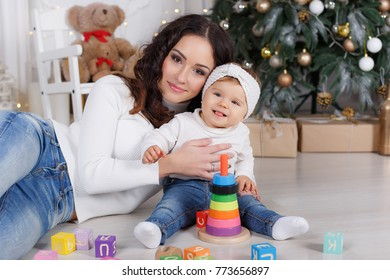 Portrait of happy mother and adorable baby celebrate Christmas. New Year's holidays. Toddler with mom in the festively decorated room with Christmas tree and decorations. Mother playing with baby girl