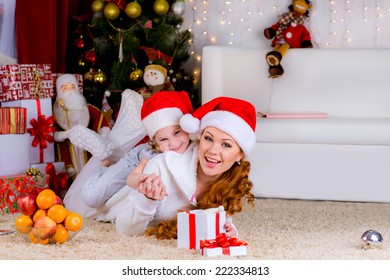 Portrait of happy mother and adorable daughter in suit of Santa's little helper near the christmas tree
