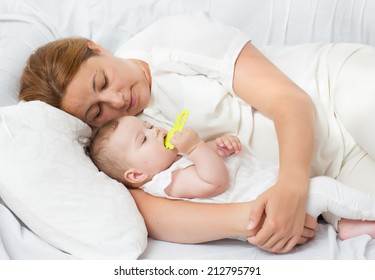 Portrait of happy mother and baby lying on the bed.