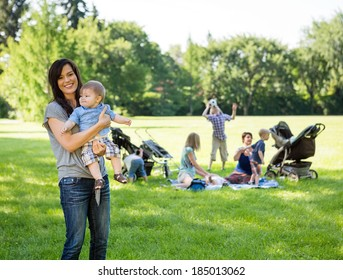 Portrait of happy mother carrying baby boy with friends and children in background at park