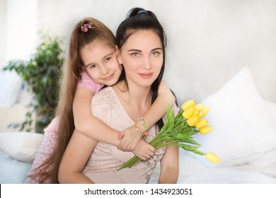 Portrait of happy mother and child daughter with flowers  in the home. Family, holidays and people concept. Happy women's day!