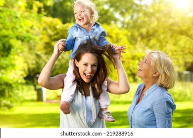 Portrait of a happy mother with child and grandmother having fun outdoors
