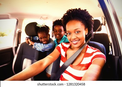 Portrait of happy mother and children sitting in car
