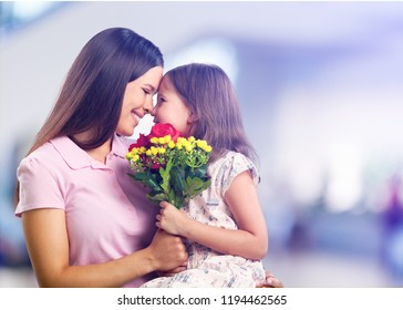 Portrait of happy mother and daughter holding  flowers - Shutterstock ID 1194462565