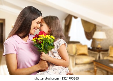 Portrait of happy mother and daughter holding  flowers