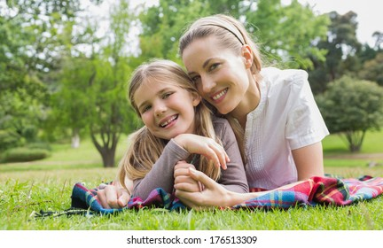 Portrait of a happy mother with daughter lying at the park
