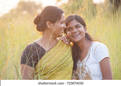 Portrait of happy mother and daughter in meadow at sunset. Smart Blurred photo