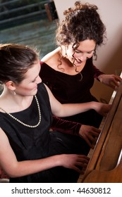 A portrait of a happy mother and daughter playing piano together
