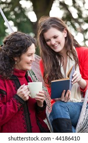 A portrait of a happy mother and daughter reading a book outdoor