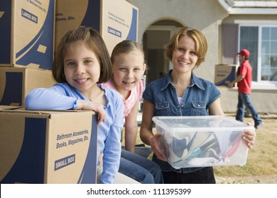 Portrait of happy mother with daughters moving into new house