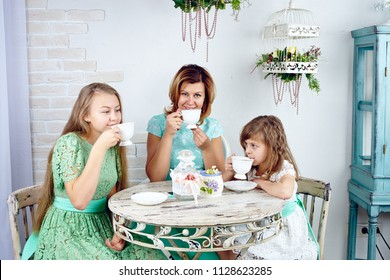 Portrait of happy mother drinking tea with her two daughters