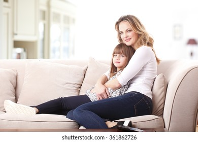 Portrait of happy mother embracing her cute daughter while sitting at living room at home. Happy family relaxing on the coach.
