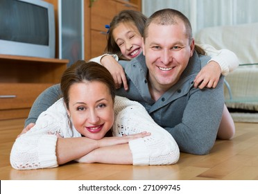 Portrait of happy mother, father and cute girl together indoors