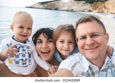 portrait of happy mother and father and two children on beach