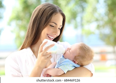Portrait of a happy mother giving bottle feeding to her baby outdoors